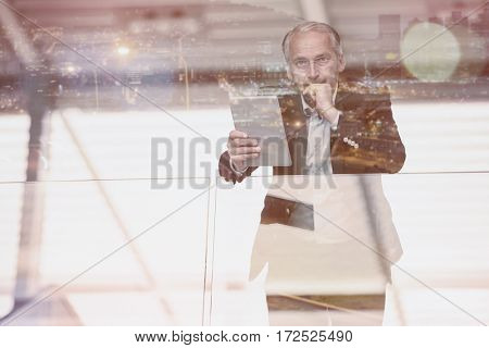 Portrait of serious businessman standing in office holding digital tablet