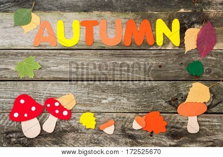 Handmade autumn frame on old wooden background. Handmade leaves mushrooms acorns and word Autumn made of felt. Top view
