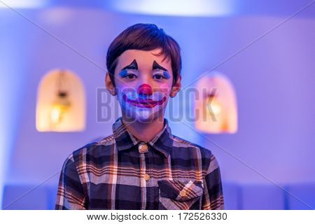 Young boy with aqua makeup on face.