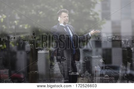 Confused businessman communicating on mobile phone at street