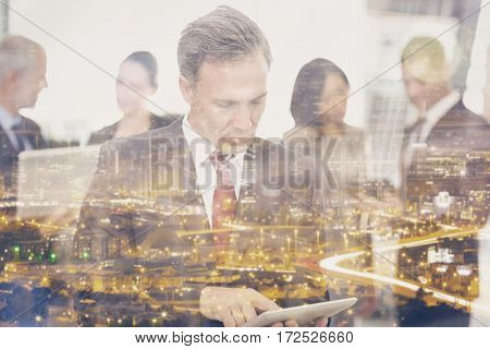 Mature businessman using digital tablet while standing at office