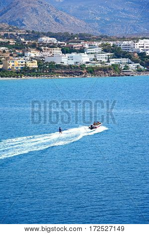 MAKRIGIALOS, CRETE - SEPTEMBER 18, 2016 - Water skier in the bay with views towards the beach and town Makrigialos Crete Greece Europe, September 18, 2016.