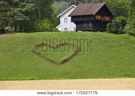 Norwegian traditional farm house and heart symbol in the countryside. Agriculture