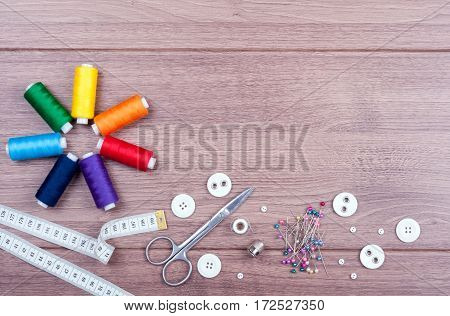 Spools with different colors of thread scissors buttons sewing supplies measuring tape and accessories for needlework on wooden background. Set for needlework top view