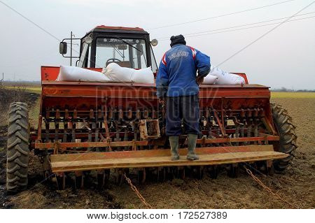 Great Dobron Ukraine - March 11 2015: A local farmer prepares the tractor to the sowing of oats on the field behind the village Great Dobron.