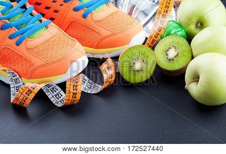 Sport shoes fruits bottle of water and measuring tape on dark background. Sport equipment. Concept healthy life sports and diet. Selective focus