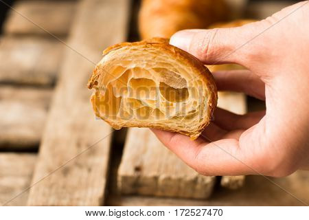Woman's hand holding freshly baked croissant cut in half flaky pastry inside visible reclaimed barn wood backgroundminimalistic stylekinfolk