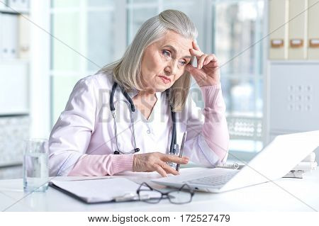Portrait of a pensive senior female doctor using laptop