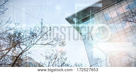 Black technology design with glow against trees and building against clear sky