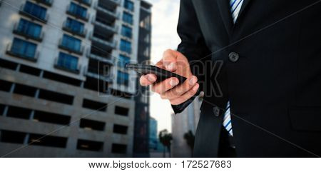 Midsection of businessman text messaging on mobile phone against glass modern building against cloudy sky