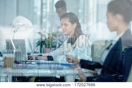 Concentrated businesswoman working on laptop in office