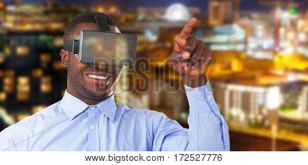 Man pointing while wearing virtual reality headset against illuminated beautiful buildings in city