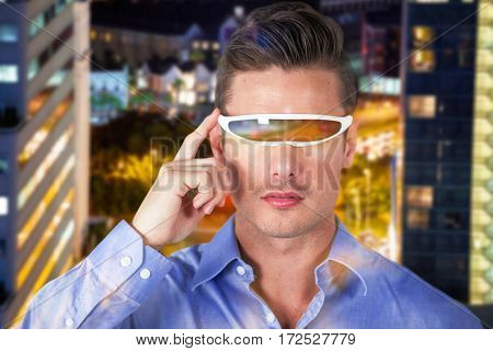 Handsome man with virtual video glasses against illuminated road amidst building at night
