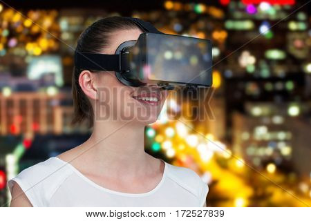 Happy woman experiencing virtual reality headset against defocused image of illuminated buildings