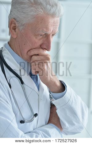 portrait of pensive senior male doctor with stethoscope