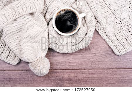 Knitted handmade wool scarf and hat. Autumn or winter womans clothes. Needlework clothes. Hot coffee cup on wooden background. Top view