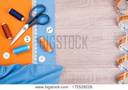 Jeans and cotton fabrics for sewing lace measuring tape and accessories for needlework on old wooden background. Spool of thread scissors buttons sewing supplies. Set for needlework top view