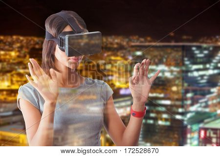 Businesswoman holding virtual glasses on a white background against high angle view of illuminated crowded cityscape