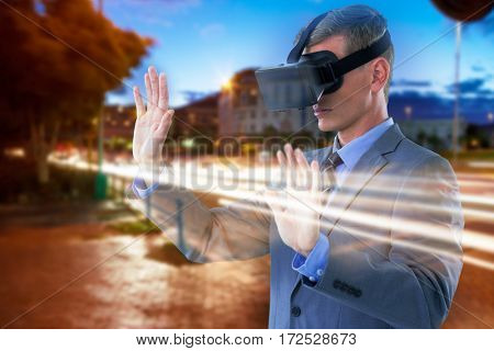 Businessman using virtual reality headset against light trails on city street