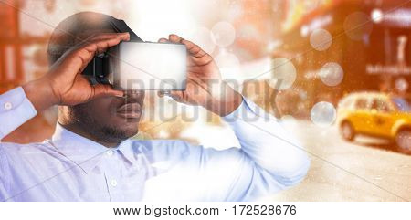 Man holding virtual reality headset against blurry new york street