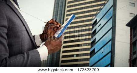 Hands of man signing document against view of modern glass office building