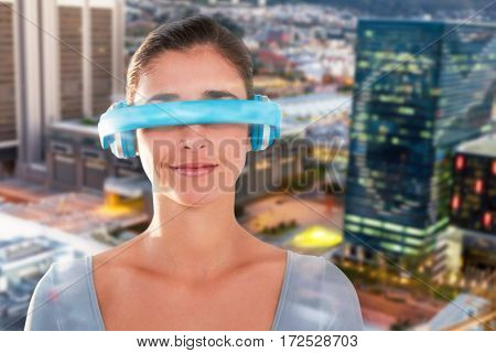 Beautiful young woman using virtual video glasses against illuminated cityscape at dusk