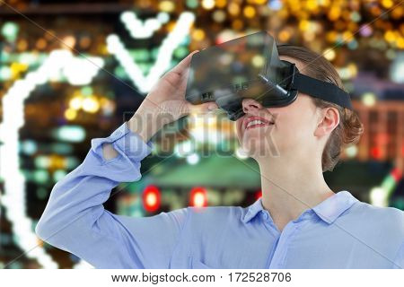 Low angle view of businesswoman using virtual reality headset against defocused image of illuminated buildings in city