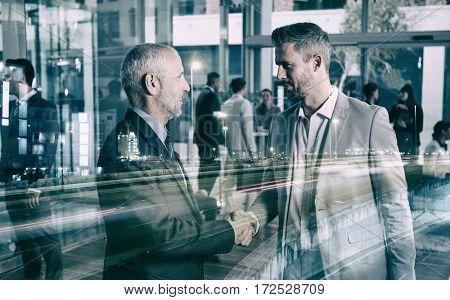 Confident businessmen shaking hands in office
