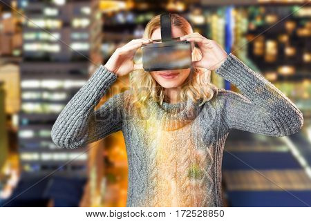 Smiling blond woman using virtual reality headset against glowing road amidst building in city at night