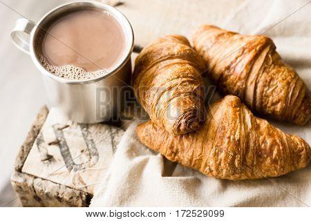 Freshly baked croissants on linen cloth aluminum mug with hot cocoa on vintage wood box cozy atmosphere kinfolk