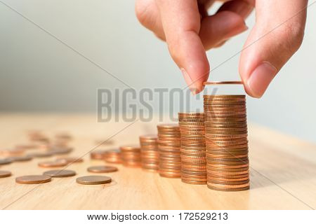 Saving money concept male hand putting money coin stack growing business or success