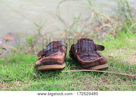 brown shoes leather old on grass select focus with shallow depth of field.