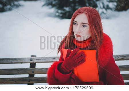 young woman with red hair in red coat in winter forest with a book.