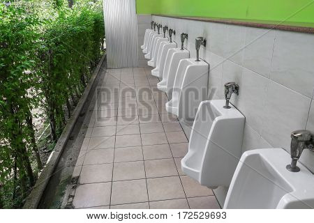row of outdoor urinal men public toilet white urinals in men bathroom
