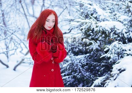 Young girl with red hair in a red dress walking in snow winter forest.