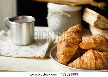 Heap of fresh croissants with gold crust on aluminum tray mug with hot cocoa or chocolate rustic wood kitchen table floral linen napkin cozy atmosphere