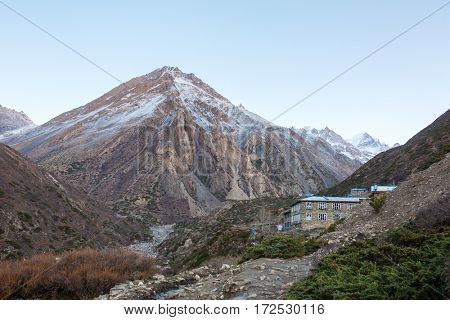 Tourists lodge on the Annapurna circuit trek with snowy mountains on background in Himalayas, Nepal