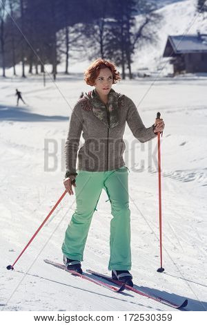 Young red-haired woman recovered at the cross-country skiing