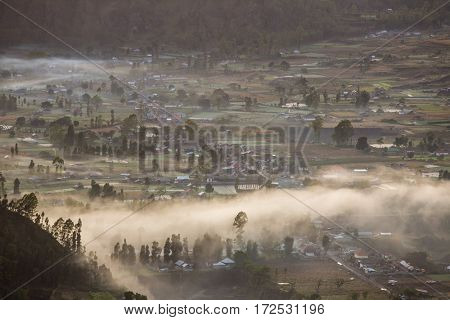 Sunrise mist over the valley with villages situated in caldera of Batur volcano in Bali, Indonesia