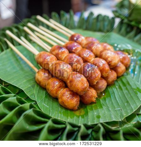 Traditional Thai style grilled Sausages on the banana leaf. Isaan pork meat sausage.