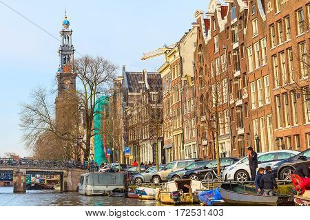 Amsterdam, Netherlands - April 1, 2016: Westerkerk or Western Church tower and dutch houses in Amsterdam, Holland