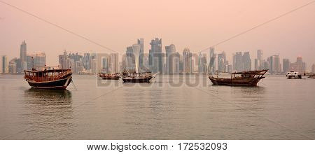 Doha, Qatar - November 2, 2016. View of Doha skyline in Qatar at dawn, with skyscrapers and dhow boats.