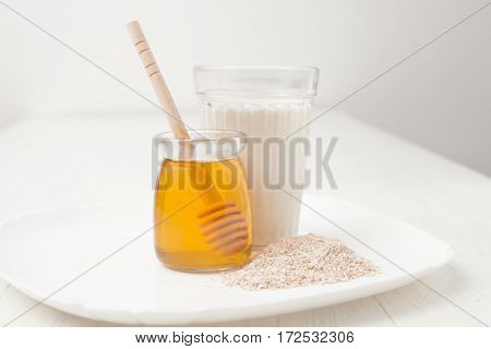 A Glass Of Milk, Oat Bran, Honey In Jar On White