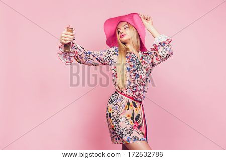 Vogue young girl posing for selfie on the pink background. Horizontal shot.