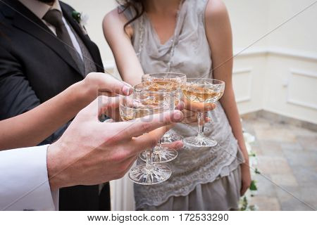 Champagne glasses. Wedding guests clinking champagne glasses with the newlywed's, outdoors. Toast.