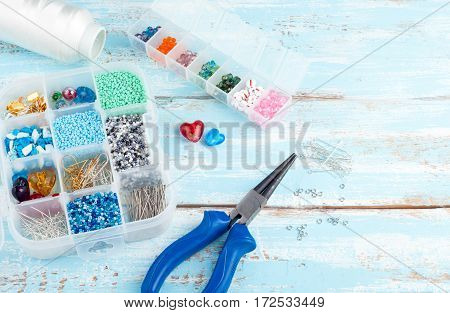 Handmade background with copyspace. Box with beads spool of thread plier and glass hearts to create hand made jewelry on old wooden background. Handmade accessories and tools