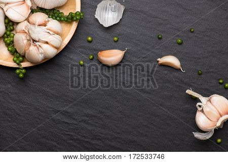 Garlic and green peppercorns on the black stone table