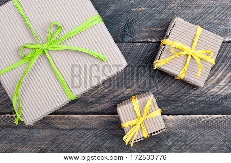 Gift boxes decorated with raffia. Gift presents on old wooden table. Top view