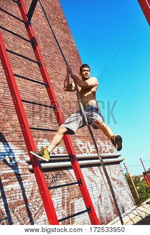 Street fitness exercise, man climbing the rope outdoors.
