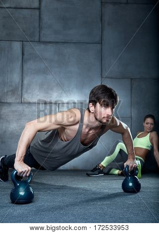 Athletic young man exercising with kettlebells in gym.